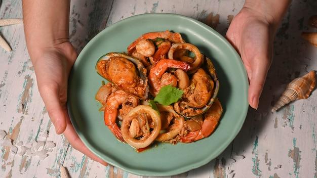 Draufsicht der weiblichen hände, die einen teller des gebratenen currypulvers der meeresfrüchte halten, thailändisches essen