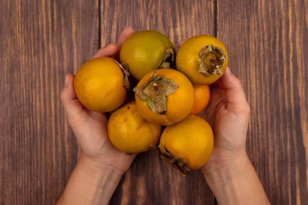 Draufsicht der weiblichen hände, die frische orange kakifrüchte auf einem holztisch halten