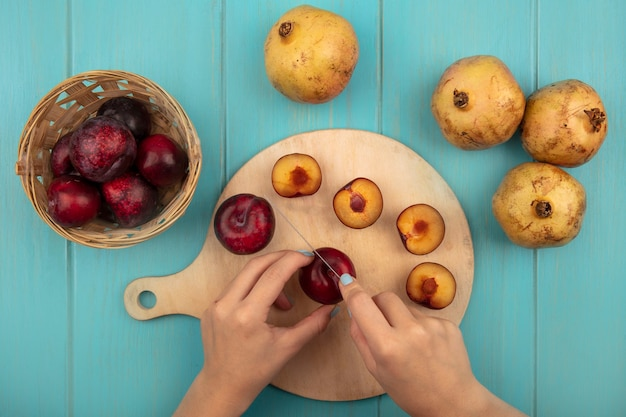 Draufsicht der weiblichen hände, die frische pluots auf einem hölzernen küchenbrett mit messer mit pluots auf einem eimer mit granatäpfeln lokalisiert auf einer blauen wand schneiden