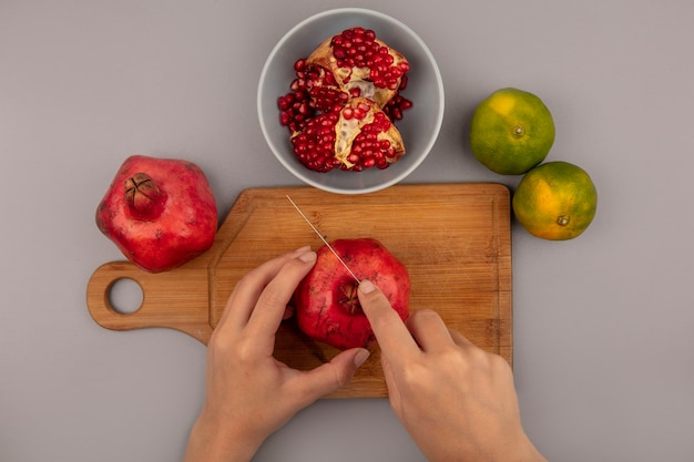 Draufsicht der weiblichen hände, die frische rote granatäpfel auf einem hölzernen küchenbrett mit messer mit offenem granatapfel auf einer schüssel mit mandarinen lokalisieren schneiden