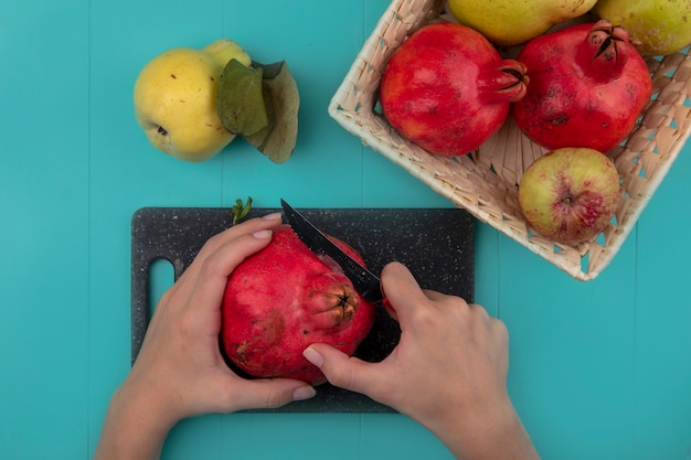 Draufsicht der weiblichen hände, die frischen granatapfel auf einem schwarzen küchenbrett mit messer auf blauem hintergrund schneiden