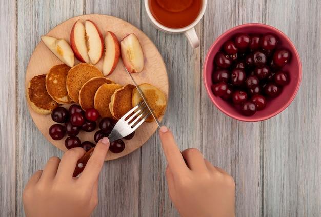 Draufsicht der weiblichen hände, die gabel und messer mit pfannkuchen und kirschen pfirsichscheiben auf schneidebrett mit schüssel kirsche und tee auf hölzernem hintergrund halten