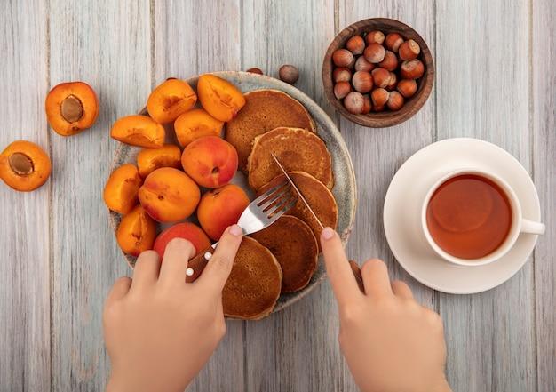 Draufsicht der weiblichen hände, die gabel und messer mit pfannkuchenteller mit ganzen und geschnittenen aprikosen und tasse tee mit schüssel nüssen auf hölzernem hintergrund halten