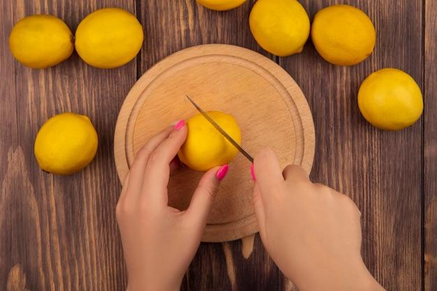 Draufsicht der weiblichen hände, die gelbe zitrone auf einem hölzernen küchenbrett mit messer auf einer hölzernen oberfläche schneiden