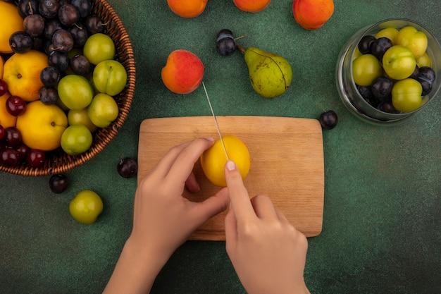 Draufsicht der weiblichen hände, die gelben pfirsich mit messer auf einem hölzernen küchenbrett auf einem grünen hintergrund schneiden