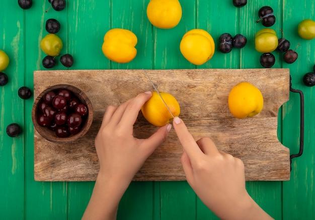 Draufsicht der weiblichen hände, die gelben pfirsich mit messer auf einem hölzernen küchenbrett mit roten kirschen auf grünem hintergrund schneiden