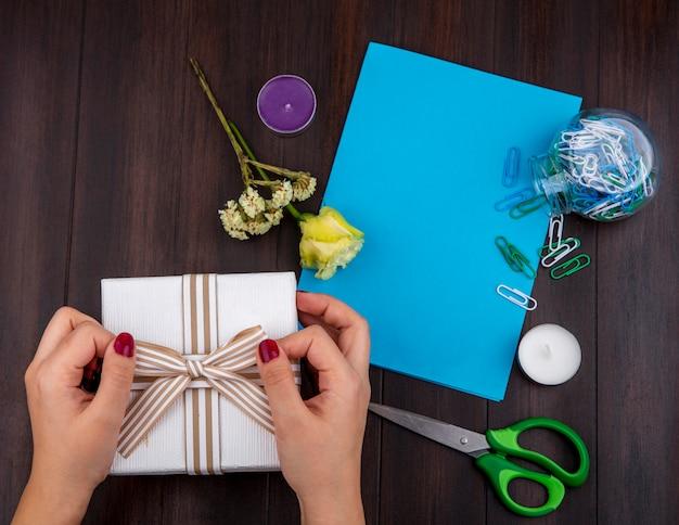 Draufsicht der weiblichen hände, die geschenkbox mit bogenband mit gelber rose auf holz mit kopienraum halten