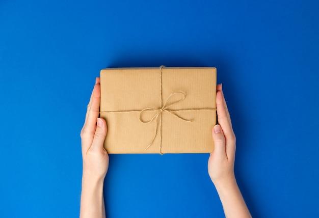Draufsicht der weiblichen hände, die geschenkboxpaket auf blauem hintergrund halten. null-abfall-einkaufskonzept. flaches banner, draufsicht, nachhaltiger lebensstil.