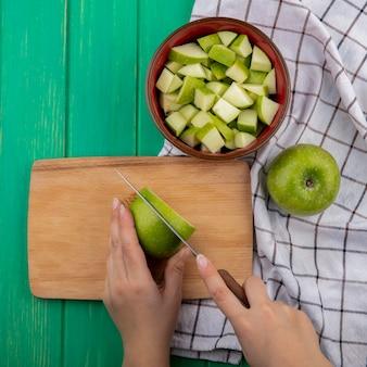Draufsicht der weiblichen hände, die grüne äpfel auf hölzernem küchenbrett auf roter schüssel gehackter äpfel und stoff hacken