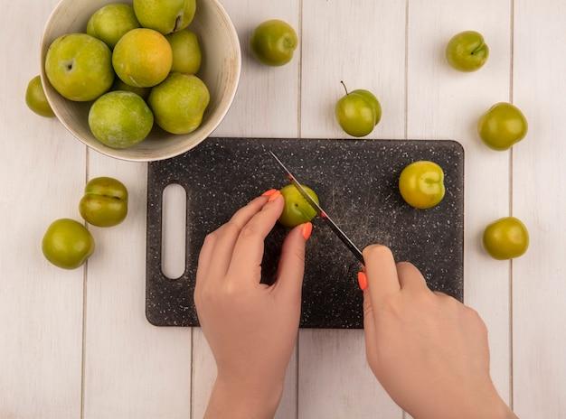 Draufsicht der weiblichen hände, die grüne kirschpflaumen auf einem küchenschneidebrett mit messer mit grünen kirschpflaumen auf einer schüssel auf einem weißen hölzernen hintergrund schneiden