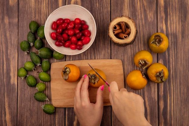 Draufsicht der weiblichen hände, die kakifrucht auf einem hölzernen küchenbrett mit messer mit kornelkirschen auf einer schüssel mit frischer kaki und feijoas schneiden, die auf einem hölzernen hintergrund lokalisiert werden