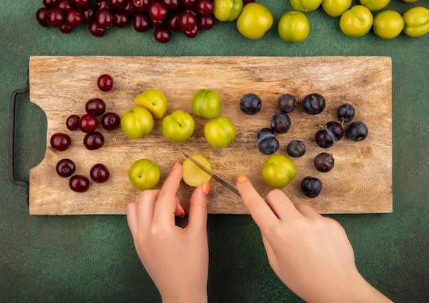 Draufsicht der weiblichen hände, die messer mit grüner kirschpflaume auf einem hölzernen küchenbrett mit roten kirschen und grünen kirschpflaumen lokalisiert auf einem grünen hintergrund halten