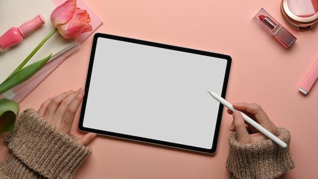 Draufsicht der weiblichen hände, die mit digitalem tablett auf rosa weiblichem arbeitsbereich mit kosmetika und blumen arbeiten
