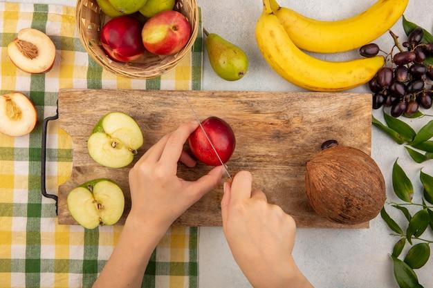 Draufsicht der weiblichen hände, die pfirsich mit messer und halb geschnittenem apfel und kokosnuss auf schneidebrett und korb pfirsichapfel auf kariertem stoff mit bananentraube und blättern auf weißem hintergrund schneiden