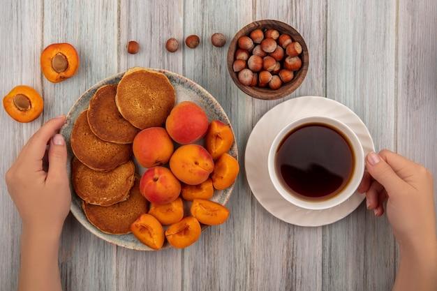 Draufsicht der weiblichen hände, die platte pfannkuchen mit ganzen und geschnittenen aprikosen und tasse tee mit schüssel nüssen auf hölzernem hintergrund halten