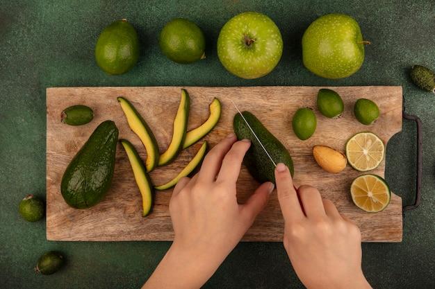 Draufsicht der weiblichen hände, die reife frische avocado mit messer auf einem hölzernen küchenbrett mit limettenfeijoas und grünen äpfeln schneiden, die auf einer grünen wand lokalisiert werden