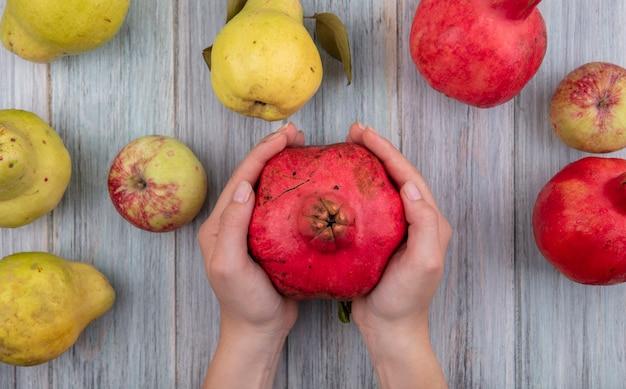 Draufsicht der weiblichen hände, die roten frischen granatapfel auf einem grauen hölzernen hintergrund halten