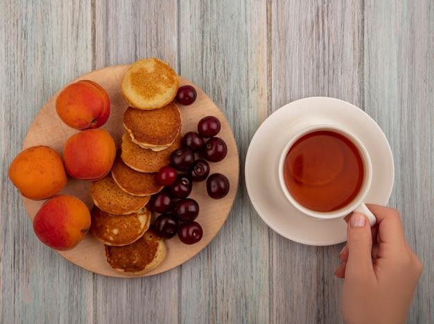 Draufsicht der weiblichen hände, die tasse tee und pfannkuchen mit aprikosen und kirschen auf schneidebrett auf hölzernem hintergrund halten