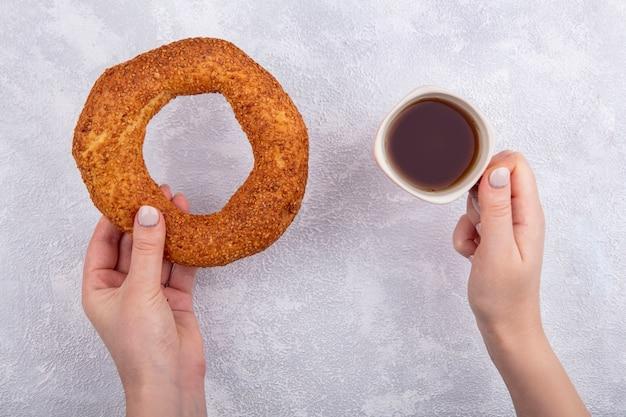 Draufsicht der weiblichen hände, die türkischen sesambagel mit einer tasse tee auf weißem hintergrund halten
