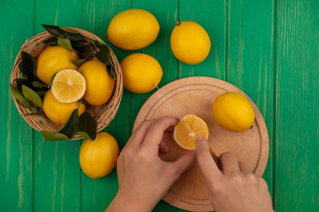 Draufsicht der weiblichen hände, die zitrone auf einem hölzernen küchenbrett mit messer mit zitronen auf einem eimer auf einer grünen holzwand schneiden