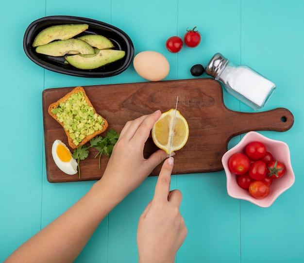 Draufsicht der weiblichen hände, die zitrone in scheiben auf hölzernem küchenbrett mit avocado-scheiben des halben eiertomaten auf schüssel auf blau schneiden