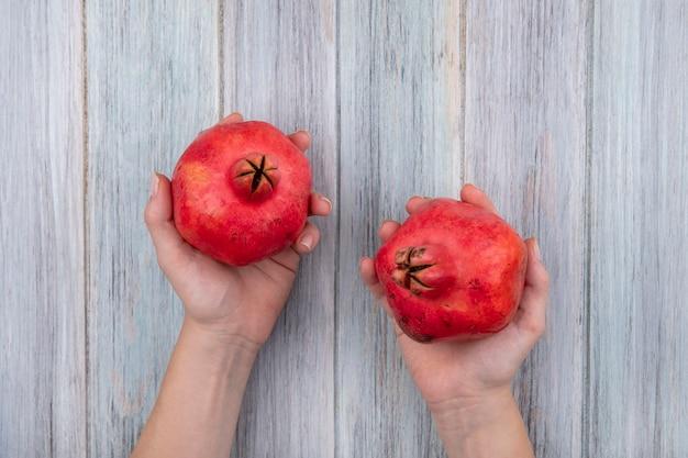 Draufsicht der weiblichen hände, die zwei rote frische granatäpfel auf einem grauen hölzernen hintergrund halten