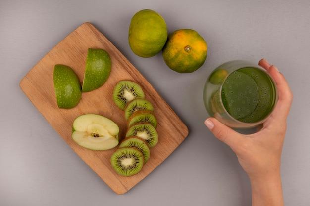 Draufsicht der weiblichen hand, die ein glas frischen kiwisaft mit gehackten scheiben der apfel-kiwi auf einem hölzernen küchenbrett mit mandarinen lokalisiert hält
