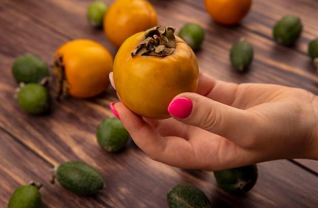 Draufsicht der weiblichen hand, die eine frische gesunde kakifrucht mit feijoas und kakifruchtfrüchten lokalisiert auf einer hölzernen oberfläche hält