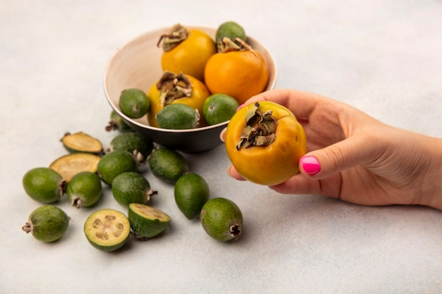 Draufsicht der weiblichen hand, die eine orange reife persimonenfrucht mit feijoas und persimonen hält, die auf einer grauen oberfläche isoliert werden