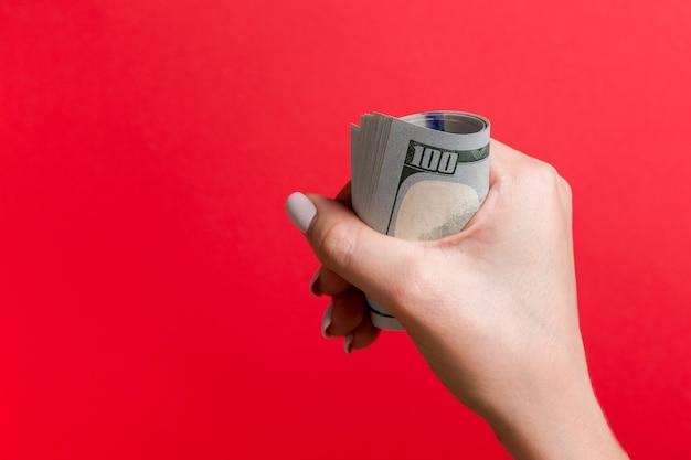 Draufsicht der weiblichen hand, die eine packung geld auf rot hält