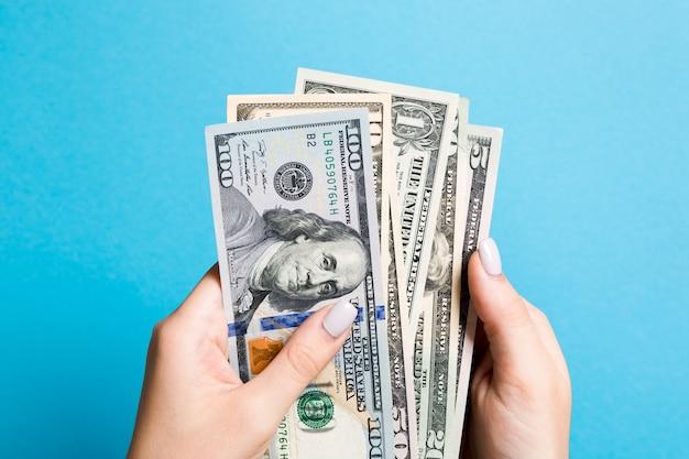 Draufsicht der weiblichen hand, die eine packung verschiedener dollarnoten auf buntem hintergrund hält. lohn- und gehaltskonzept