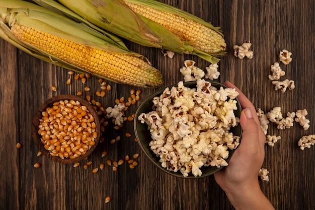 Draufsicht der weiblichen hand, die eine schüssel popcorn mit maiskörnern auf einer holzschale mit frischen körnern auf einem holztisch hält
