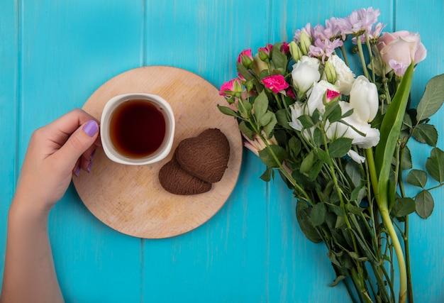 Draufsicht der weiblichen hand, die eine tasse tee auf einem hölzernen küchenbrett mit wunderbaren frischen blumen lokalisiert auf einem blauen hölzernen hintergrund hält