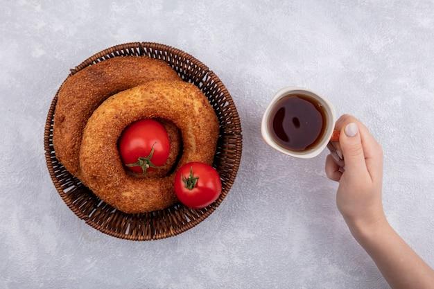 Draufsicht der weiblichen hand, die eine tasse tee mit einem eimer des türkischen bagels auf einem weißen hintergrund hält