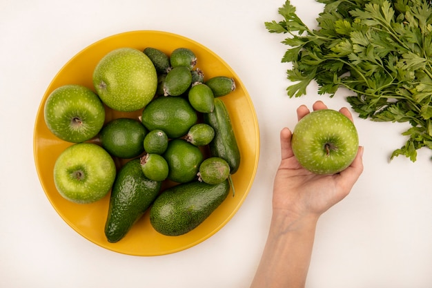 Draufsicht der weiblichen hand, die einen apfel mit gelbem teller von frischen früchten wie äpfeln feijoas und avocado auf einer weißen oberfläche hält
