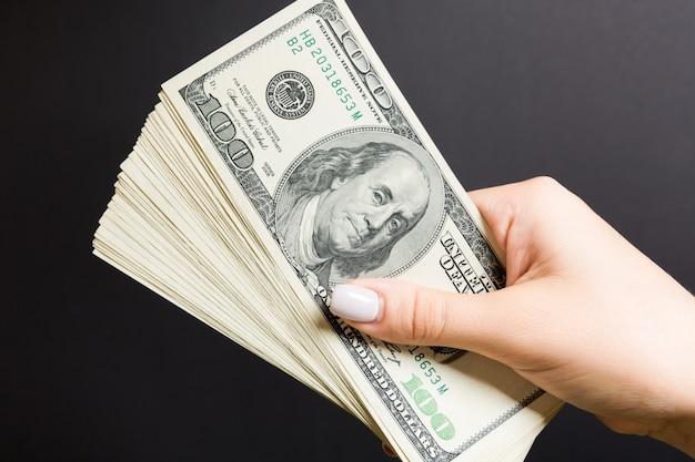Draufsicht der weiblichen hand, die einen fächer von einhundert dollar hält. darlehenskonzept. wohlstandskonzept