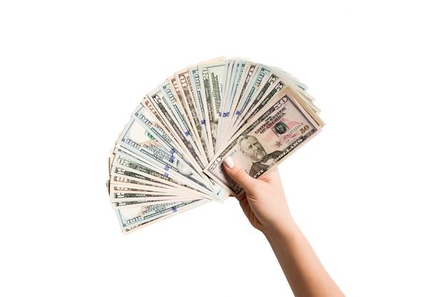 Draufsicht der weiblichen hand, die einen fan von dollarnoten auf isoliert gibt. profit- und luxuskonzept