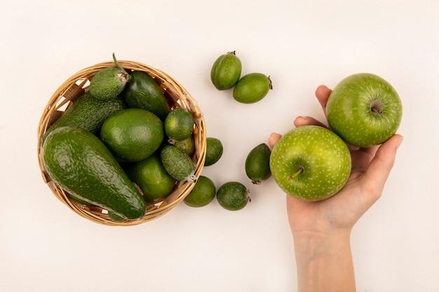 Draufsicht der weiblichen hand, die frische äpfel mit feijoas und avocados auf einem eimer auf einer weißen oberfläche hält
