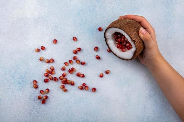 Draufsicht der weiblichen hand, die halbe kokosnuss mit roten granatapfelkernen auf weiß hält