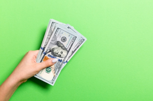 Draufsicht der weiblichen hand, die hundert dollarnoten auf grün gibt