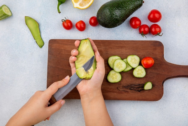 Draufsicht der weiblichen hand, die in einer hand avocado und in der anderen handi messer über hölzernen küchenbrett mit gurkenscheiben kirschtomaten zitrone lokalisiert auf weiß hält