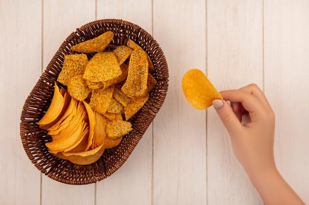 Draufsicht der weiblichen hand, die knusprige chips mit einem eimer würziger chips auf einem beigen holztisch hält