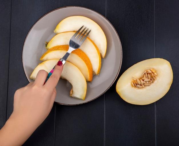 Draufsicht der weiblichen hand, die melonenscheibe mit gabel auf platte auf schwarz nimmt