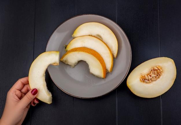 Draufsicht der weiblichen hand, die melonenscheibe mit scheiben auf platte auf holz hält
