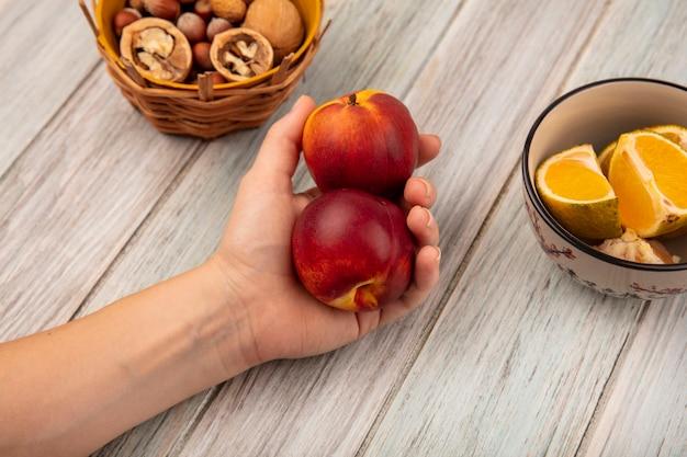 Draufsicht der weiblichen hand, die pfirsiche mit nüssen auf einem eimer mit mandarinen auf einer schüssel auf einer grauen holzoberfläche hält