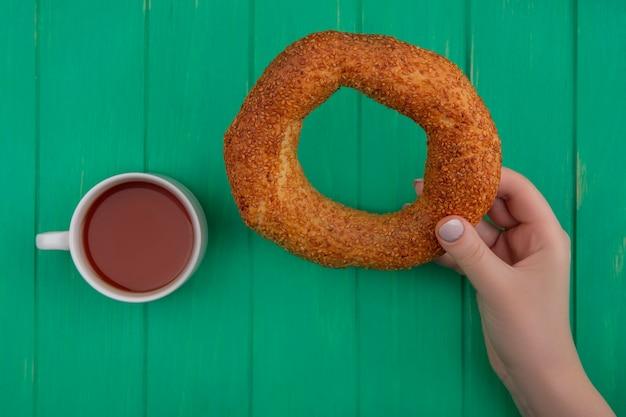 Draufsicht der weiblichen hand, die traditionellen türkischen bagel mit einer tasse tee auf einem grünen hölzernen hintergrund hält