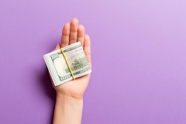 Draufsicht der weiblichen hand, die viele aufgerollte dollarbanknoten auf buntem hintergrund hält. armutskonzept. kreditkonzept mit kopierraum