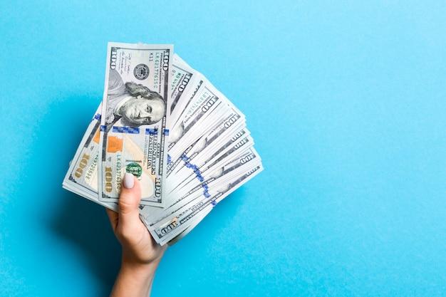 Draufsicht der weiblichen hand einen fan des geldes auf buntem hintergrund halten. einhundert dollarnoten. kredit- und schuldenkonzept mit kopienraum