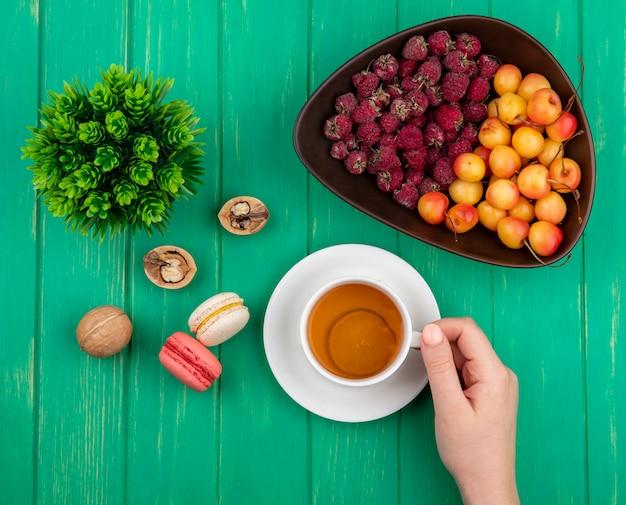 Draufsicht der weiblichen hand hält tasse tee mit himbeeren und weißen kirschen in einer schüssel mit macarons auf einer grünen oberfläche