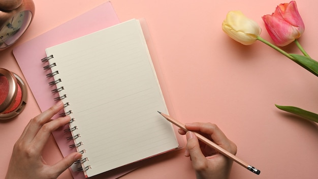 Draufsicht der weiblichen hand mit bleistiftschrift auf leerem notizbuch auf rosa weiblichem arbeitsbereich mit blume